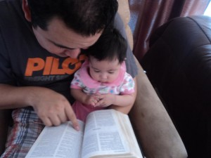 daddy reads bible to baby
